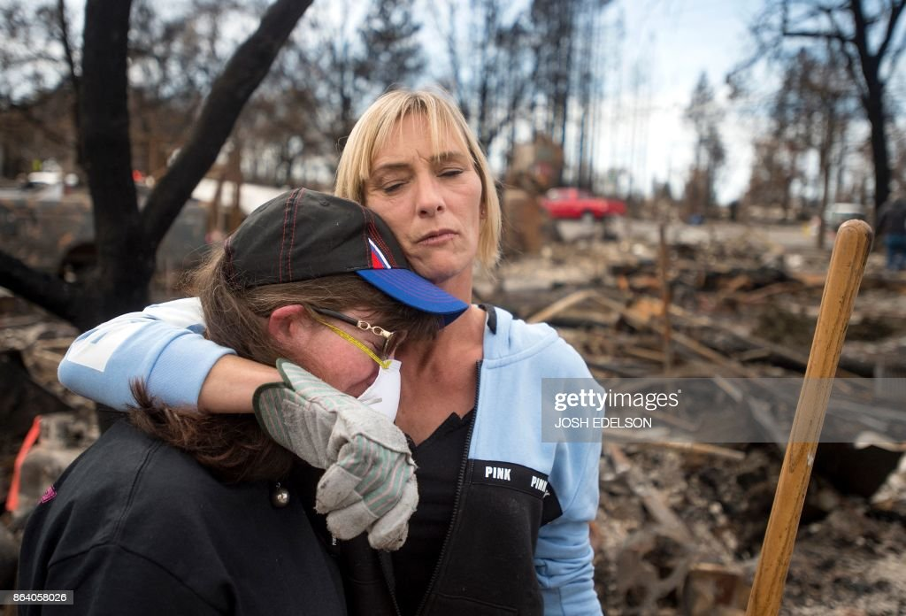 TOPSHOT - Tanya Williams (R) consoles her neighbour Dawn Lockhart (L) as they view their burned homes in the Coffey Park area of Santa Rosa, California, on October 20, 2017. Residents are being allowed to return to their burned homes on October 20 to grieve and search through remains. Around 5,700 homes and businesses have been destroyed by the fires, the deadliest in California's history. /