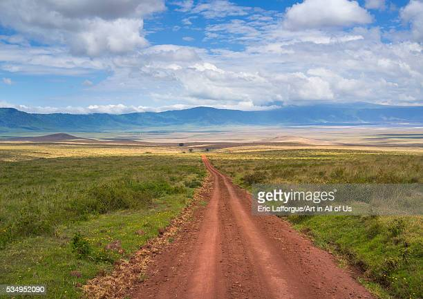 Tanzania Arusha Region Ngorongoro Conservation Area a dirt track dissecting a vast short grass savannah plain surrounded by a volcano caldera wall