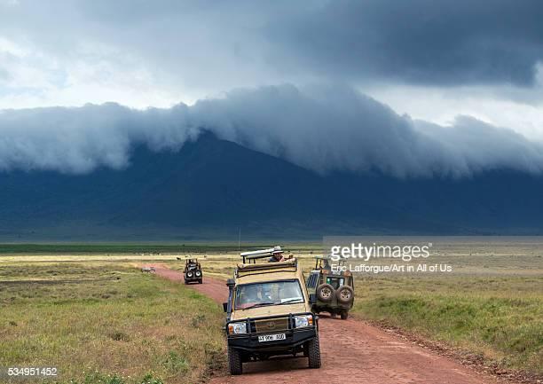 Tanzania Arusha Region Ngorongoro Conservation Area a safari vehicle crosses the savannah plain on the floor of a volcano caldera