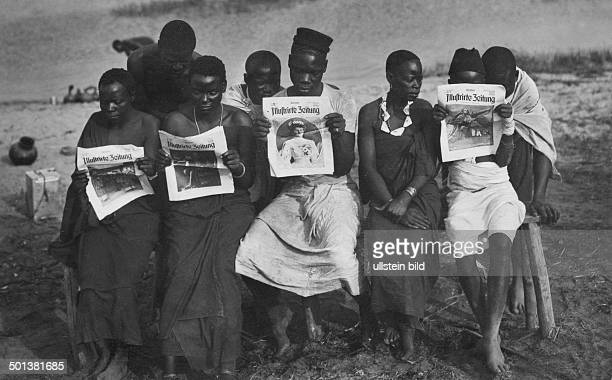 African population Indegenous people read the 'Berliner Illustrirte Zeitung' newspaper in German East Africa undated probably 1914 Photographer...