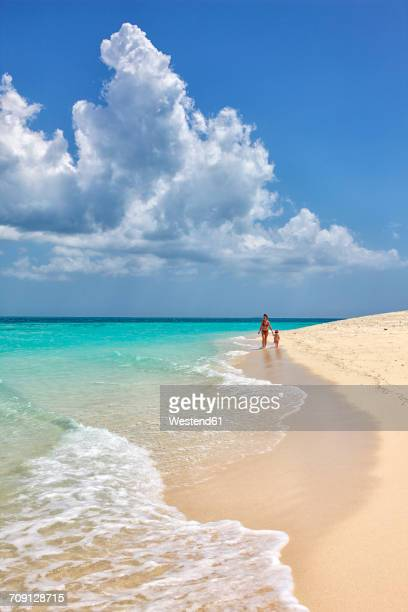tanzania, zanzibar island, unguja, niamembe island, mother and little daughter strolling on the beach - zanzibar island stock photos and pictures