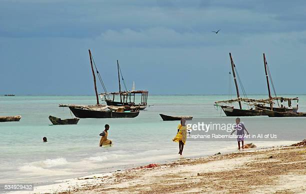 Tanzania, Zanzibar, Nungwi, children playing in turquoise sea by traditional fisherman boat on white beach