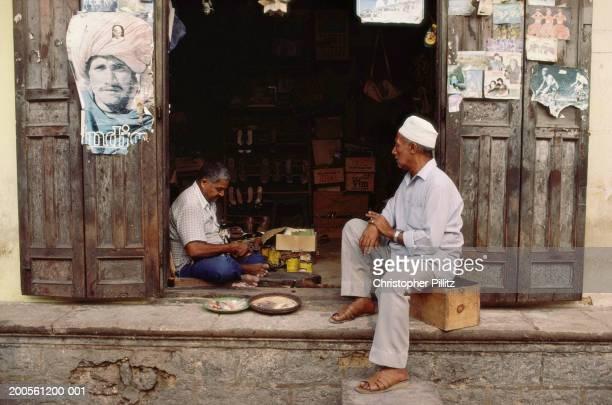 Tanzania. Zanzibar, Two men sitting in shop entrance