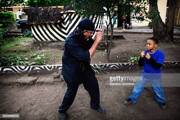 Pete O'Neil shadow boxes with the young son of his deceased close friend Geronimo Pratt on the eve of his memorial inside his Tanzania compound Pratt...