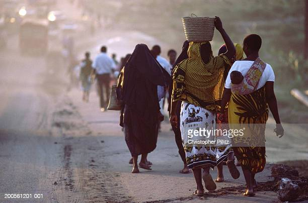 Tanzania,Dar es Salaam city,people walking along dusty road,rear view