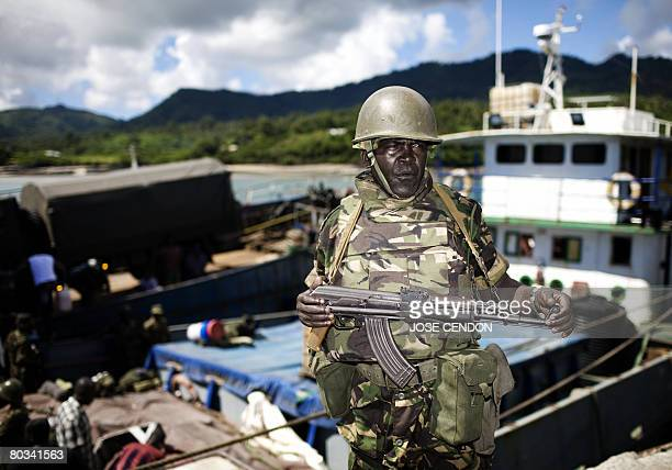A Tanzanian African Union soldier waits to be transferred to a military camp after disembarking at the port of Fomboni the capital Moheli on March 22...