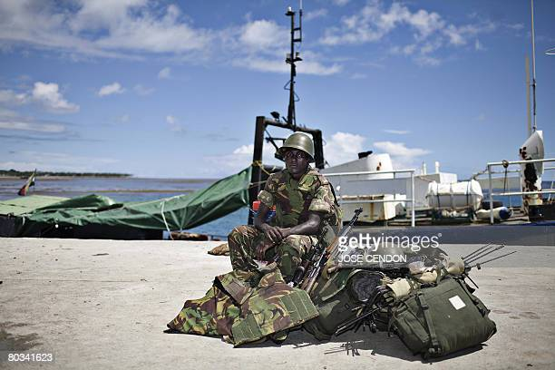 A Tanzanian African Union soldier waits with his gears to be transferred to a military camp after disembarking at the port of Fomboni the capital of...