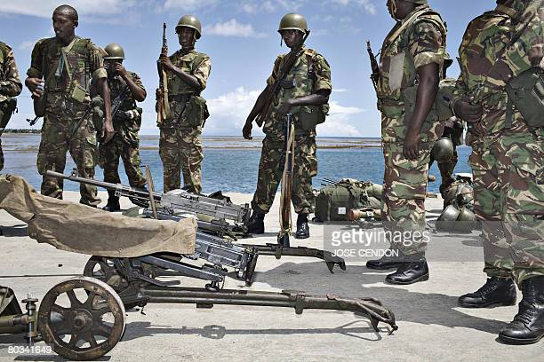 Tanzanian African Union troops wait with their gears to be transferred to a military camp after disembarking at the port of Fomboni the capital of...