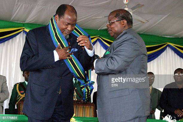 Tanzanian President Benjamin Mkapa decorates his Mozambique counterpart Joaquim Chissano who is retiring in December as the leader of the southern...