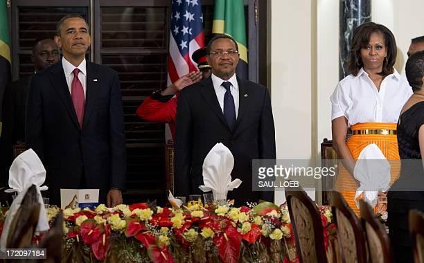 Tanzanian President Jakaya Kikwete stands alongside US President Barack Obama and US First Lady Michelle Obama as a band plays the Tanzanian National...
