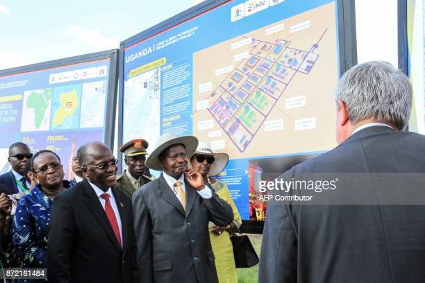 Tanzanian President John Magufuli and Ugandan President Yoweri Kaguta Museveni stand in front the project board for the construction of the East...