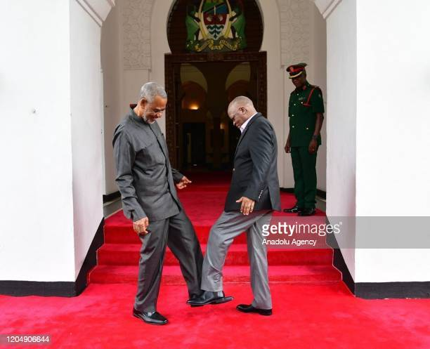 Tanzanian President John Magufuli greets Tanzanian opposition politician Maalim Seif Sharif Hamad by tapping his feet against theirs to avoid...
