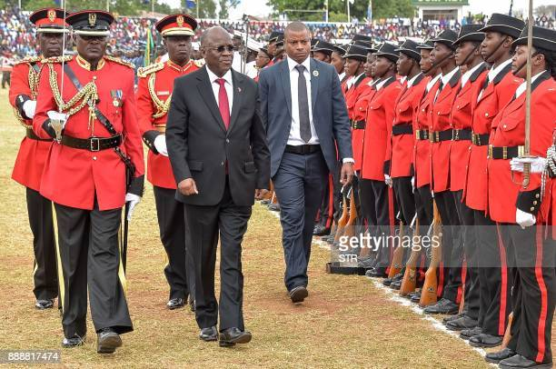 Tanzanian President John Pombe Magufuli reviews an honour guard of troops as he attends a ceremony marking the country's 56th independence...