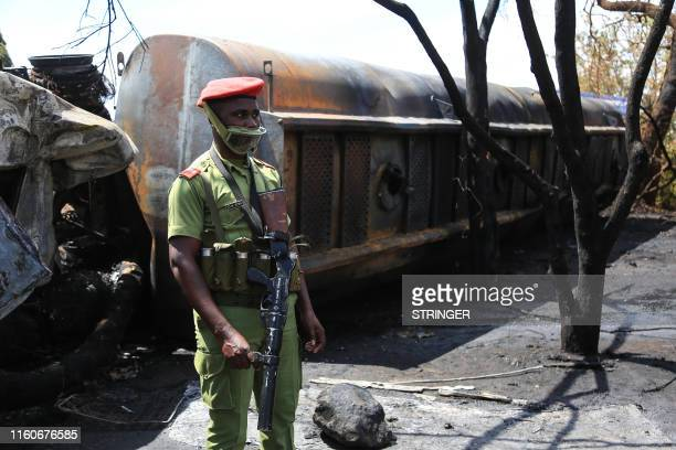 Tanzanian security officer controls the area where the carcass of a burnt out fuel tanker is seen along the side of the road following an explosion...