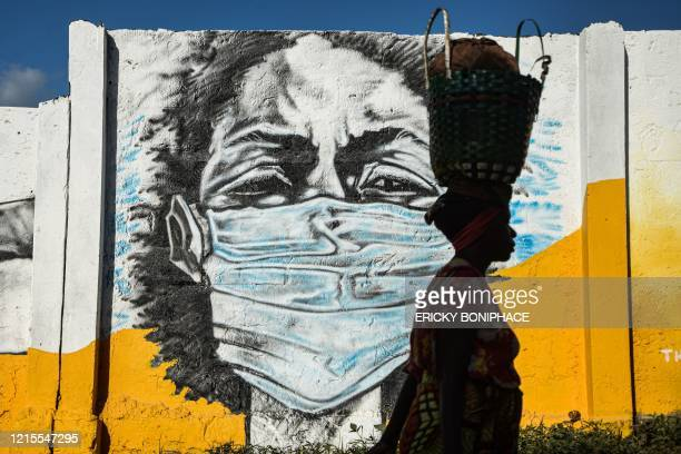 Tanzanian woman carries a basket on her head as she walks in front of a graffiti painted by the Wachata artists group to raise awareness about...