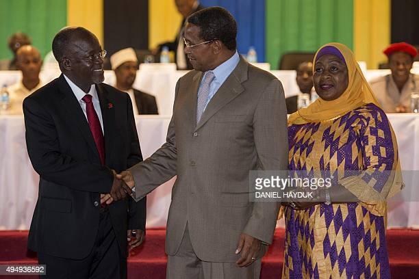 Tanzania's outgoing President Jakaya Kikwete shakes hands with Presidentelect John Magufuli flanked by Vice Presidentelect Samia Suluhu during an...
