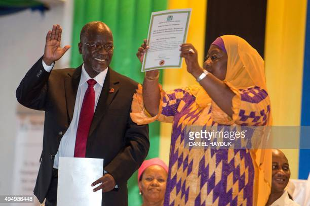 Tanzania's Presidentelect John Magufuli gestures as Vice Presidentelect Samia Suluhu holds up a certificate during the official election announcement...