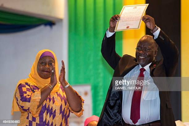 Tanzania's Vice Presidentelect Samia Suluhu applauds as Presidentelect John Magufuli holds up his official certificate of victory at the election...