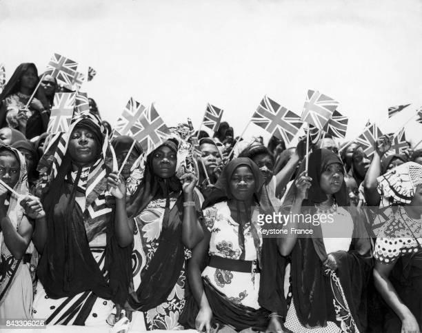 Tanzaniennes avec des drapeaux anglais lors de la visite de la princesse Margaret en Tanzanie le 11 octobre 1956