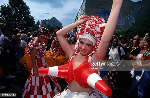 Tanzende Frau mit zwei rotweissenVerkehrskegeln vor der Brust und einemHut aus rotweissen Absperrungsbändern büstenhalter bh kegel verkehrskegel