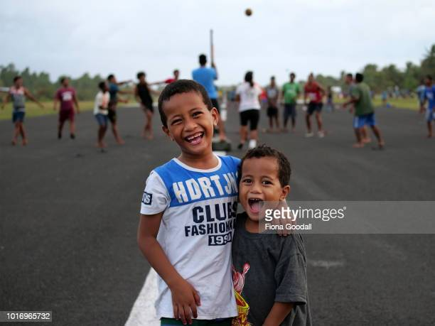 Tao and Joshua Dao pose for a photograph on the airport runway as a volleyball game is underway on August 15 2018 in Funafuti Tuvalu The small South...