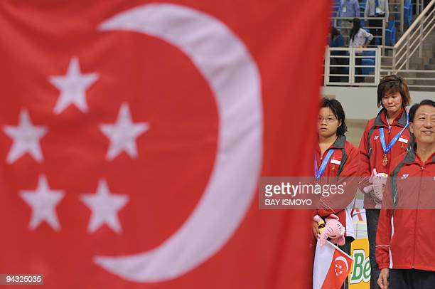 Tao Li and Shana Lim of Singapore look at their country's flag during the awards ceremony for the women's 100m backstroke swimming final at the 25th...