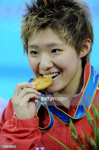 Tao Li of Singapore poses with the gold medal won in the Women's 50m Butterfly final during day six of the 16th Asian Games Guangzhou 2010 at Aoti...
