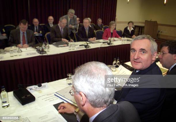 Taoiseach's Bertie Ahern takes his seat opposite the First Minister David Trimble with his Irish Ministers at Armagh City Hotel for the fourth...