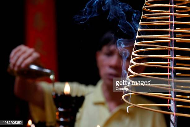Taoist temple. Emperor Jade pagoda . Incense spiral burning and taoist worship rituals with oil. Ho Chi Minh City. Vietnam.