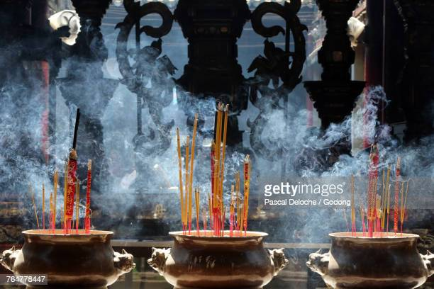 Taoist temple. Phuoc An Hoi Quan Pagoda. Incense sticks on joss stick pots are burning and smoke used ftopay respect to the Buddha. Ho chi Minh City. Vietnam.