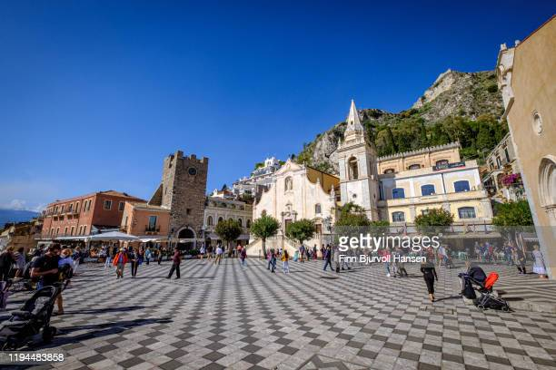 taormina main square piazza ix aprile filled with tourists, the church chiesa di san giuseppe in the background - finn bjurvoll stockfoto's en -beelden