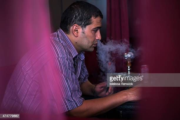 Taoufik Nour smokes from a hookah pipe at The Desert Rose Restaurant and Hookah Lounge, which serves non-tobacco shisha. Hailing from Morocco, Nour...