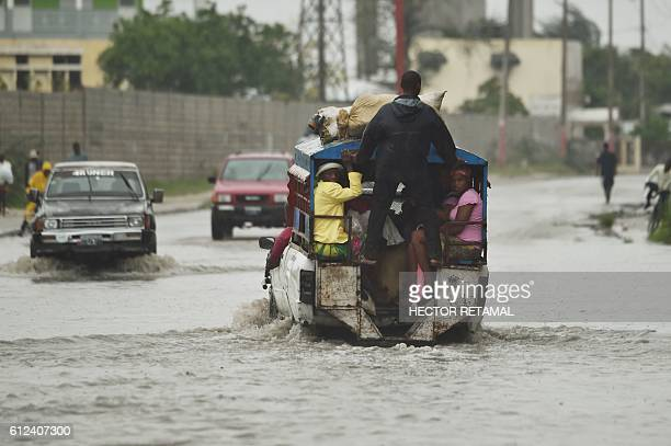 A tap tap crosses the water left by the rain after hurricane Matthew in PortauPrince on October 4 2016 Hurricane Matthew made landfall in...