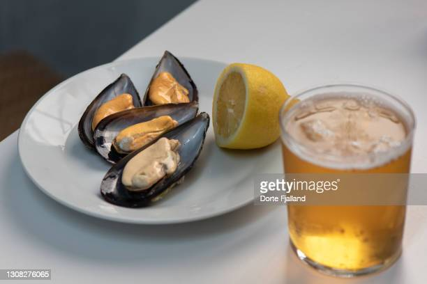 a tapa of a few fresh mussels with lemon and a cold beer - dorte fjalland fotografías e imágenes de stock
