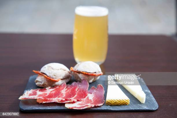 Tapas and beer served on a slate
