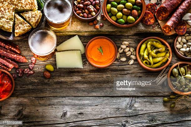tapas and beer: typical spanish food shot from above making a frame - olive pimento stock photos and pictures