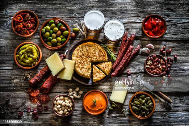 tapas and beer: typical spanish food shot from above on rustic wooden table - antipasto stock pictures, royalty-free photos & images