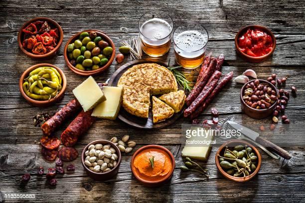 tapas y cervezas: comida típica española rodada sobre mesa rústica de madera - cultura española fotografías e imágenes de stock
