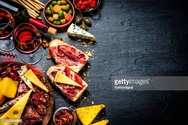 tapas and red wine background on black table. copy space - spanish culture stock pictures, royalty-free photos & images