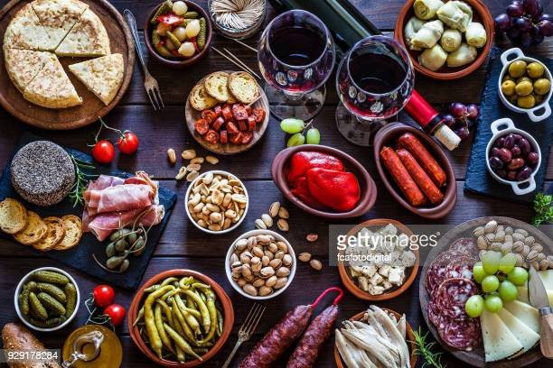 tapas and wine on rustic wooden table shot from above - tapas stock photos and pictures