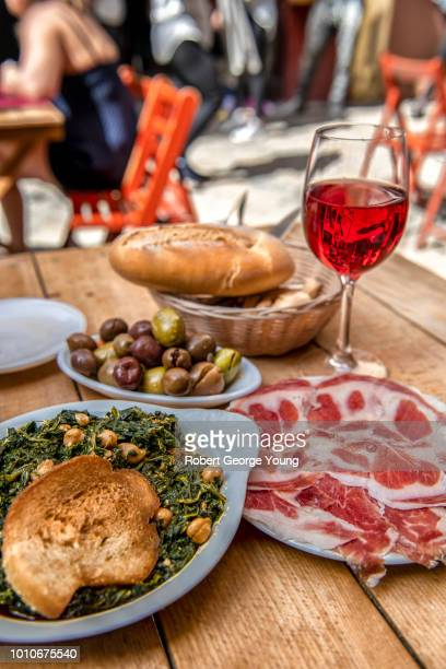 tapas at an outside restaurant table with other tables in the background. in the foreground espinacas con garbanzos (spinach with chickpeas), jamon ibericos (ham), olives, bread and rosé wine. - tapas stock photos and pictures