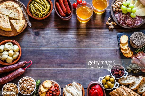 tapas frame on rustic wooden table - delicatessen stock photos and pictures