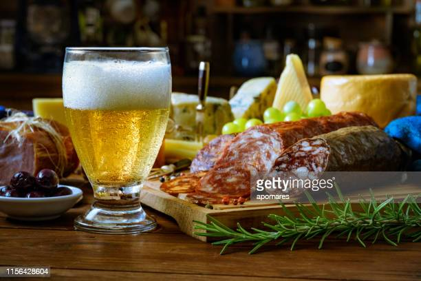 tapas of cheese, cured ham, salami, beer and chorizo on a rustic wooden table - salumeria stock photos and pictures
