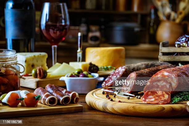 tapas of cheese, cured ham, salami wine and chorizo on a rustic wooden table - antipasto stock pictures, royalty-free photos & images