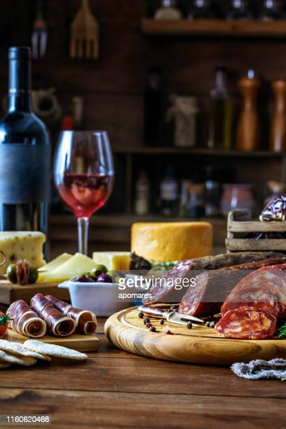 tapas of cheese, cured ham, salami wine and chorizo on a rustic wooden table - italian food stock pictures, royalty-free photos & images
