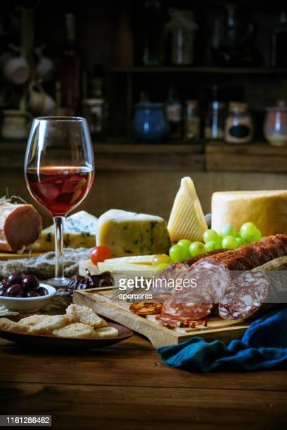 tapas de queso, jamón curado, vino de salami y chorizo sobre una mesa rústica de madera - cultura española fotografías e imágenes de stock