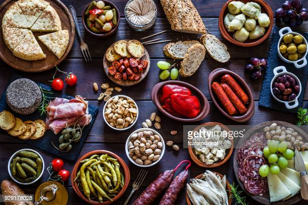 tapas on rustic wooden table shot from above - tapas stock photos and pictures
