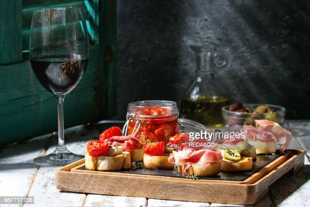 Tapas or bruschetta variety Bread with ham prosciutto sun dried tomatoes olive oil olives pepper on slate wood board with glass of red wine over...