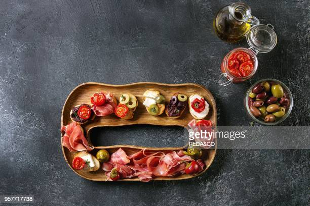 Tapas or bruschetta variety Crusty bread with ham prosciutto sun dried tomatoes olive oil olives pepper on decorative wooden plate over dark texture...