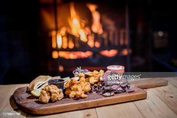 tapas snack board un soir d'hiver avec le feu dans le sol arrière. - plan moyen angle de prise de vue photos et images de collection